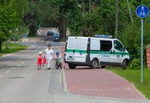 Gājēja ar bērniem apiet Reģionālās pašvaldības policijas auto, kas aizšķērsojis gājēju ietvi.