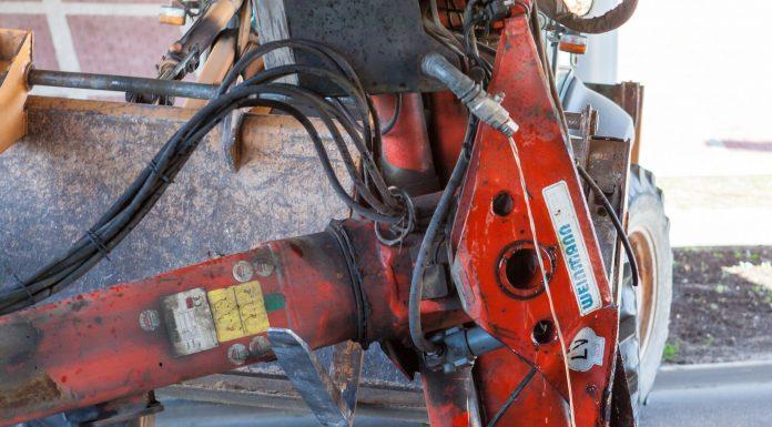 No nolauztā manipulatora uz asfalta seguma līst hidrauliskā eļļa.